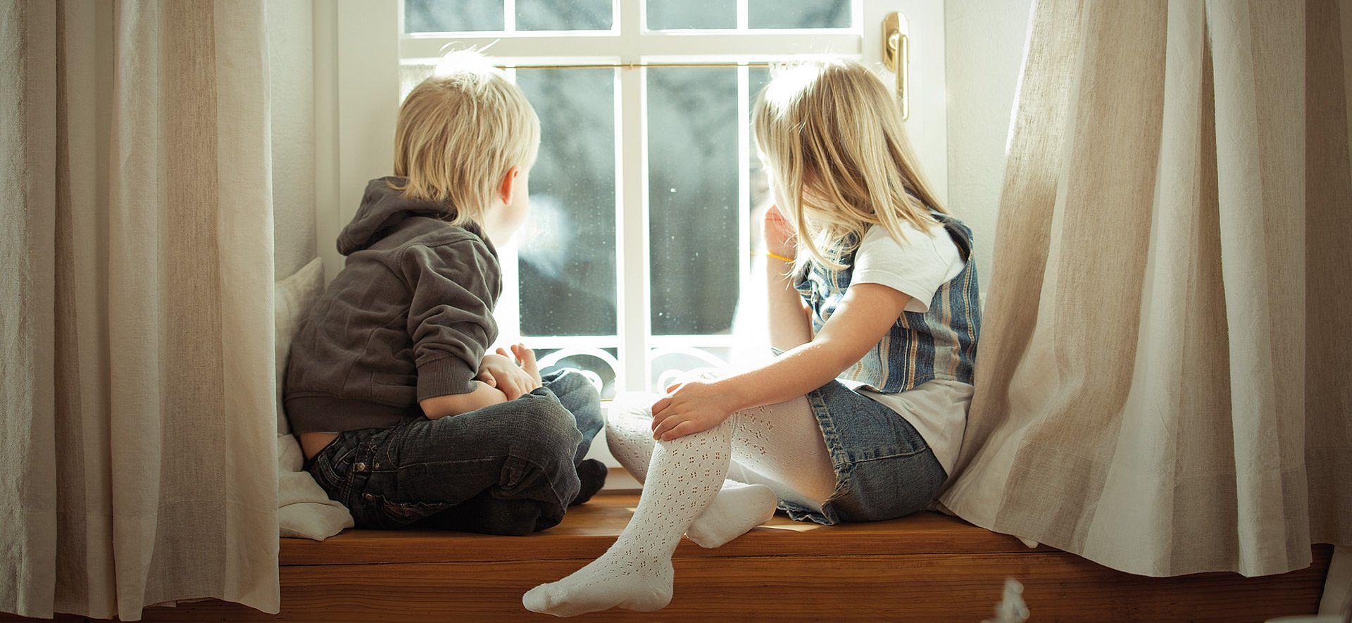 Kinder auf Fensterbank sitzend